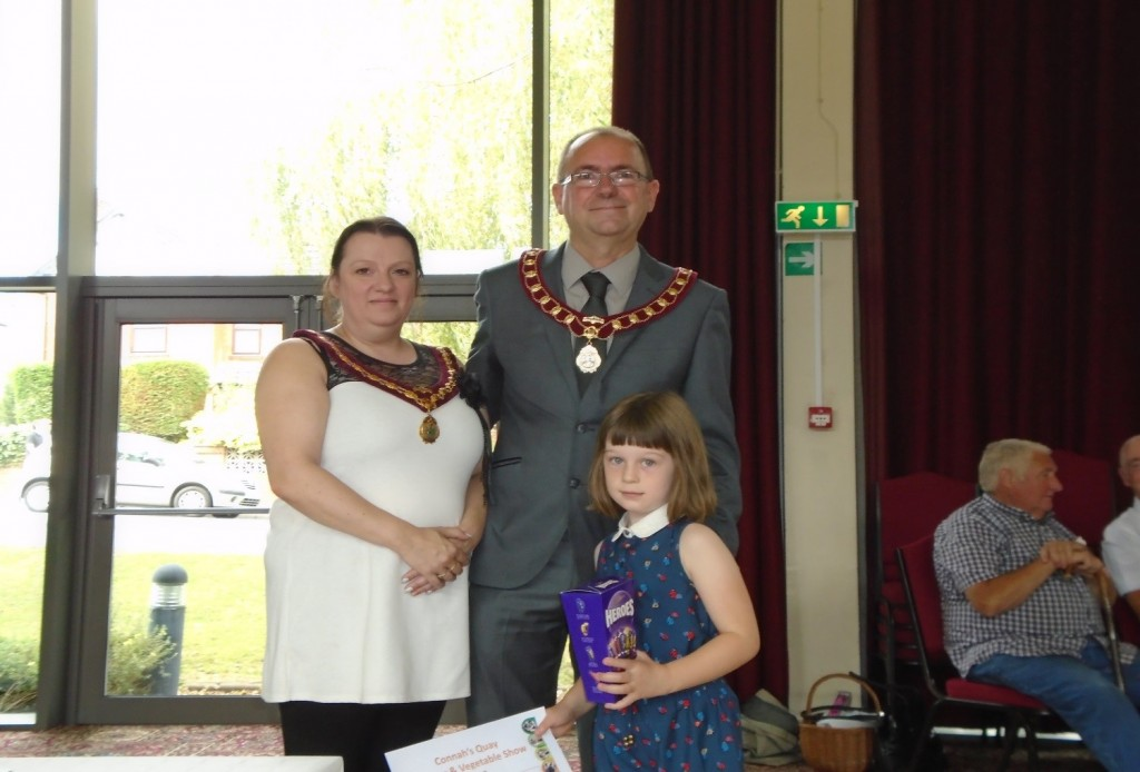 Mia Roberts receives her prize for the best in children's section from Cllr Martin White and Vice-Chair consort          Mrs White